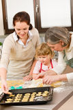 3 generations women prepare dough for baking. Happy little girl rolling out dough with mum and grandmother Stock Photo