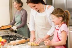 3 generazioni di donne che cuociono i grafici a torta di mela Fotografie Stock