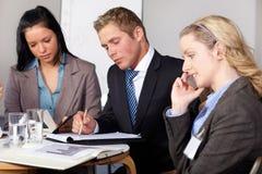 3 genti di affari che lavorano ad alcuni calcoli Fotografia Stock