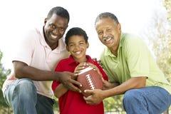 3 gerações no parque com futebol americano Imagens de Stock Royalty Free