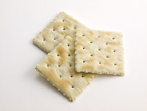 3 gezouten gestapelde Crackers op wit Stock Foto's
