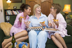3 girlfriends at home eating pizza. Laughing royalty free stock image