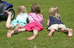 3 Girls. Lying on grass enjoying summer royalty free stock images
