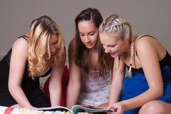 3 girls in pajama reading a magazine on bed Stock Photo