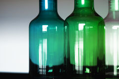 3 glass bottles green blue and clear. White, Green and blue glass bottles. Empty. Sidelit on whte base with white background royalty free stock photo