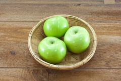 3 green apples on basket with teak wood background Stock Image