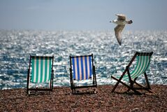 3 Green and Blue Beach Chairs on Brown Sea Shore Stock Photos