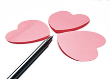 3 harten en en een pen Stock Foto's