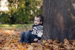 3 Jahre alte Kind, die auf dem goldenen Blatt sitzen Lizenzfreie Stockfotos