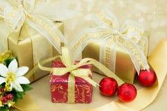 3 julklappar med röda baubles. Arkivbild