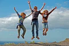 3 Jump for Joy. 3 kids jumping joyfully at the edge of a cliff, with the sea and sky behind them in the distance. The children are a brother and his younger stock photography