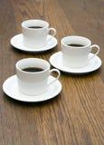 3 kaffekoppar table trä Arkivfoto
