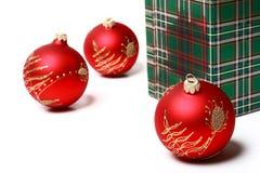 3 Kerstmisballen en groene gift Royalty-vrije Stock Afbeeldingen