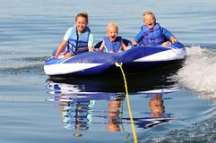 3 Kids on Water Tube. 3 Excited Kids Riding Water Tube on Lake Stock Image