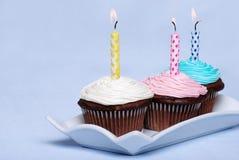 3 magdalenas coloridas del chocolate del cumpleaños Imágenes de archivo libres de regalías