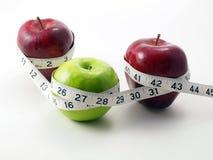 3 manzanas rodeadas con la cinta de medición Foto de archivo libre de regalías