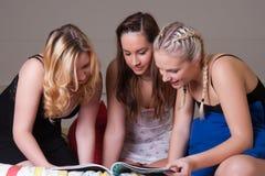 3 meisjes die in pyjama een tijdschrift op bed lezen Stock Foto