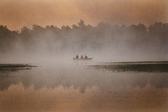 3 men in a boat. Three men fishing on a foggy morning in a boat Stock Photos