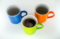 3 mokken, 1 met groene koffie. Stock Foto's