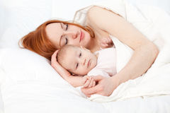 3 months old baby boy with mother in bed Royalty Free Stock Photos