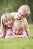 3 niños que juegan afuera Imágenes de archivo libres de regalías