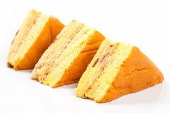 3 parties de gâteau jaune sur un fond blanc Photographie stock