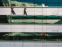3 People Hanging on White High Rise Building during Daytime Royalty Free Stock Images