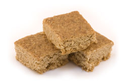 3 pieces of flapjack. Three square pieces of golden flapjack (or tray bake) arranged in a neat pile, isolated on a clean, white backdrop Royalty Free Stock Image