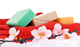 3 pieces of soap and a flower. 3 pieces of soap, different colors and a flower on red towel, spa style Stock Image