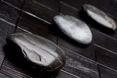 3 river rocks on black wood Royalty Free Stock Photos