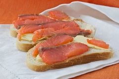 3 sandwiches with salmon. 3 sandwiches with butter and salmon lying on white   linen napkin Royalty Free Stock Image