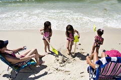 3 Shovels. Three little girls and two mommies enjoying a day at the beach.  Each of the girls are holding a green shovel Stock Photography