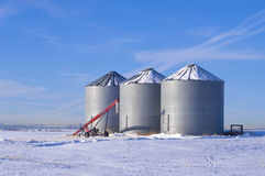 3 Silo's with auger. Storage silos with farming equipment; good background for winter and agricultural topics Stock Image