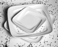 3 square shaped plates. Black and white picture of square shaped serving plates stacked  with two big and one smaller one. Confetti sprinkled around it Stock Images