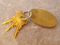 3 tasti dell'oro e keychain in bianco sulle mattonelle Immagini Stock Libere da Diritti