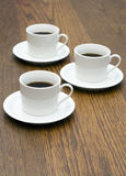 3 tazas de café en el vector de madera Foto de archivo