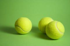 3 tenisowy piłek ond zieleni tło Obrazy Royalty Free
