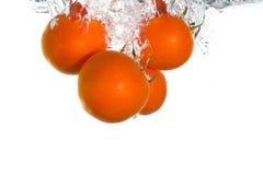 3 tomaten die in water vallen Stock Afbeeldingen