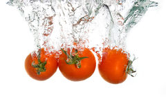 3 tomates que caen en agua Fotos de archivo libres de regalías