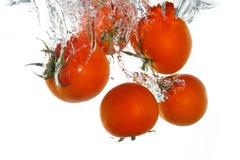 3 tomates que caen en agua Imágenes de archivo libres de regalías