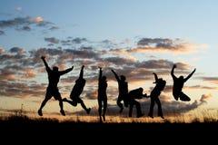 3 vänner som hoppar silhouettes Fotografering för Bildbyråer