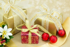 3 Weihnachtsgeschenke mit rotem Flitter. Stockfotografie