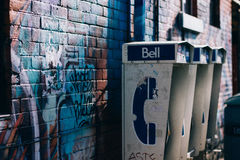 3 White and Blue Bell Telephone Booth Beside Brown Concrete Wall Stock Image