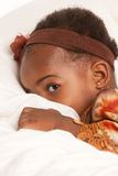 3 year old African American girl sit on bed Stock Images