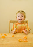 3 year old boy eating. 3 year old boy eats an orange he has peeled himself Royalty Free Stock Image