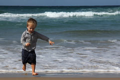3-year-old child running away from the waves Stock Images