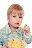 3-year-old kid eating cornflakes. Boy at breakfast cornflakes and invites you to try Stock Photo