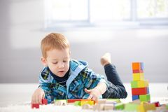 3 year old playing with cubes on floor Stock Photo
