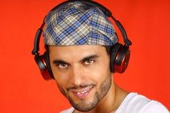 30岁有贝雷帽和耳机的人 库存照片