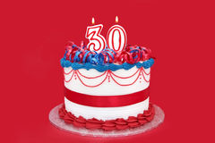 30th Cake. Cake with 30th candles, on vibrant red background Stock Images